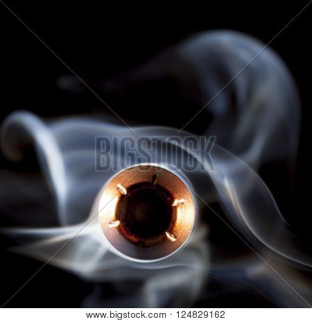 Hollow point bullet with copper coating and smoke coming at the viewer