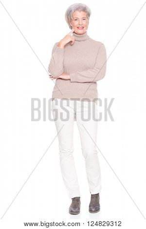 Senior woman standing in front of white background