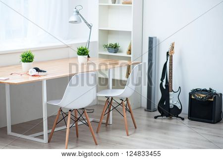 Music world.  View of a nice specious room with big table standing near the window and the guitar standing on the floor