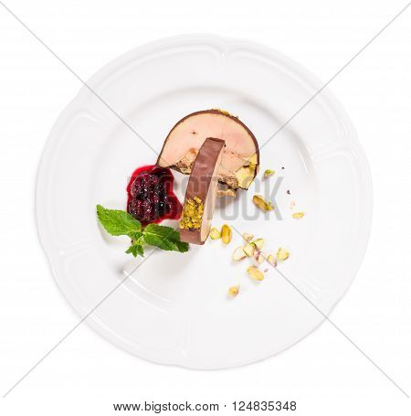 Delicious foie gras covered with dark chocolate and pistacchio nuts with red berry jam and mint. Isolated on a white background. poster