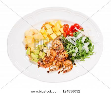 Jumbo shrimp salad with avocado mango topped with pine nuts and parmesan cheese. Isolated on a white background.