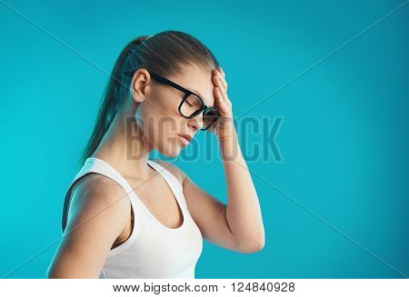 Young female having hangover or vertigo. Studio portrait over blue background. Concept of pain, symptom and health care.