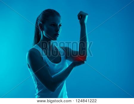 Elbow injury indicated with red spot on woman's arm. Health care, medicine and treatment.
