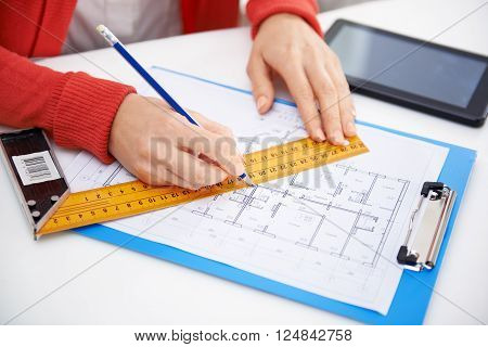 Close-up of woman architect drawing and measuring construction plan in her office. Woman designer with ruler and pencil working on house sketch.
