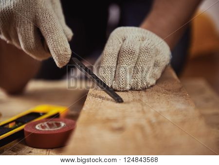 Male carver's hands with chisel working with beam in workshop. Skilled craftsman carving wood.