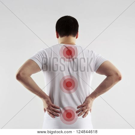 Acupressure and back treatment concept. Young man with backache touching his loin.