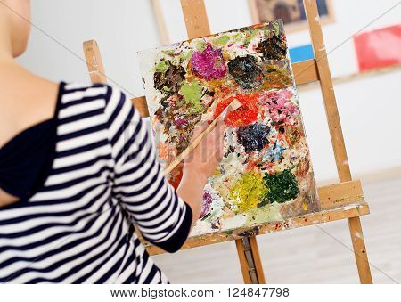 Close-up of woman hand drawing picture with brush and colorful oil paints. Young female painter working at easel in her artistic studio.