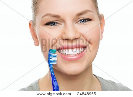 Dental cure. Cavity protection. Close-up portrait of happy female with toothy smile holding brush over white background.
