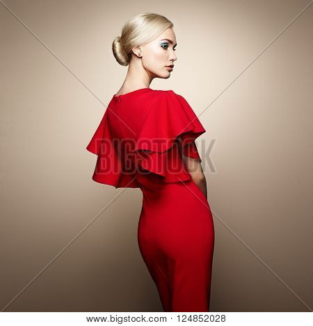 Fashion portrait of elegant woman with magnificent hair. Blonde girl. Perfect make-up. Girl in elegant red dress. Girl posing. Studio photo