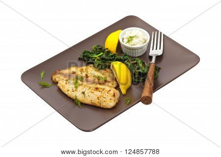 Baked Fish Fillet with Sauteed Spinach on white background. Selective focus.