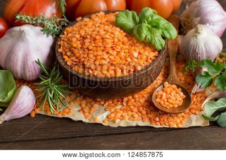 Red lentils in a bowl with tomatoes garlic and herbs on wood