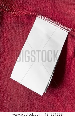 Blank white clothes label on red cloth as a background