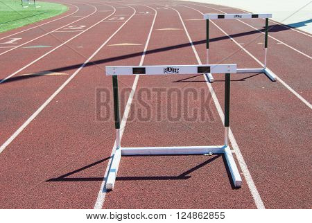 Two hurdles on a running track placed on lanes at the end of a straight away with the bend in sight.