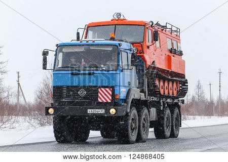 NOVYY URENGOY, RUSSIA - APRIL 16, 2013: Blue off-road truck URAL 5323 carries the all-terrain vehicle TTM-3902 Taiga at the interurban road during a snowfall.