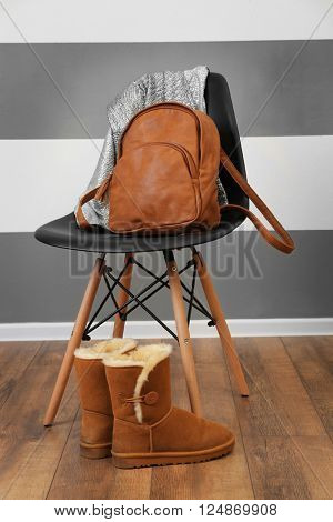 Brown leather backpack and shirts on chair near boots indoors