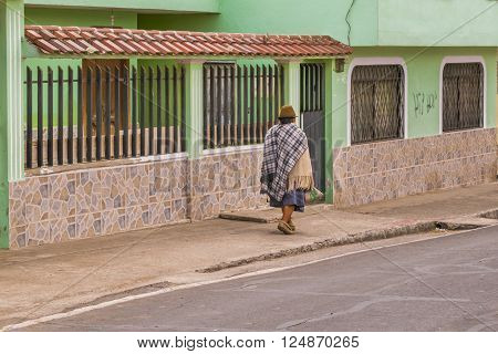 QUITO, ECUADOR, OCTOBER - 2015 - Ecuadorian indigenous adult woman with traditional clothing walking on a street in a poor village near Otavalo in Ecuador, South America.