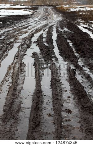 dirty dirt road with big ditches and puddles