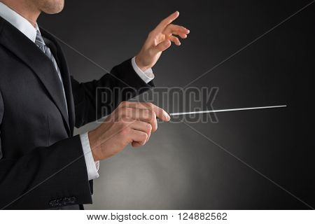 Person Directing With A Conductor's Baton On Grey Background