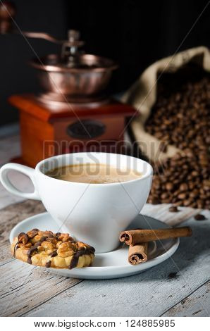 Coffee, roasted beans, mill grinder and cookie with nuts on wooden background