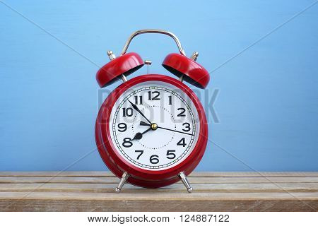 Red retro alarm clock on on a blue background. The sound of the alarm. Just in time. Empty space for Your text.