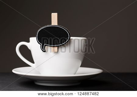 White cup of morning coffee with black thought cloud for messege on it.