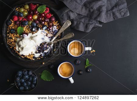 Healthy breakfast. Oat granola crumble with fresh berries, seeds and ice-cream in iron skillet pan on dark wooden board and cups of coffee over black backdrop, top view, copy space