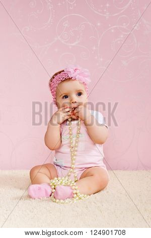 Little girl sitting on the floor holding a pearl necklace.