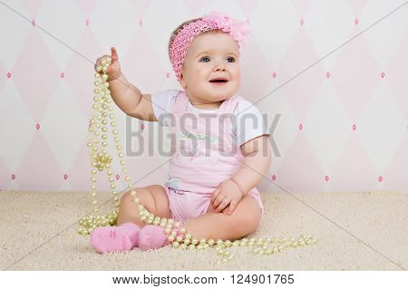 Little girl sitting on the floor holding a pearl necklace