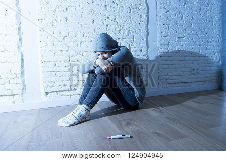 young red hair teenager girl or young woman in shock and overwhelmed after positive pregnancy test sitting on home floor devastated and depressed in youth unwanted maternity concept
