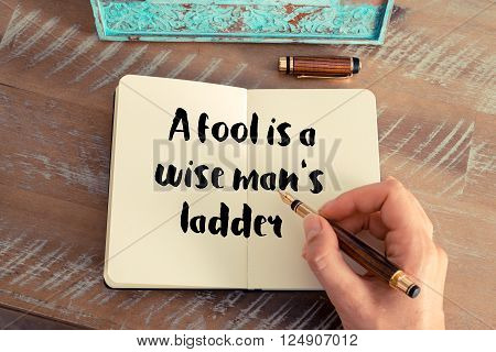 Retro effect and toned image of a woman hand writing on a notebook. Handwritten quote A fool is a wise man's ladder as inspirational concept image