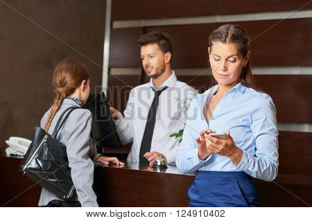 Concierge at hotel reception serving guests with woman checking her smartphone