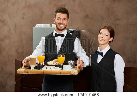 Waiter staff team serving breakfast in a hotel restaurant