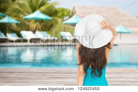 people, summer holidays, travel, tourism and vacation concept - woman in swimsuit and sun hat from back over exotic hotel resort beach with swimming pool and sunbeds background