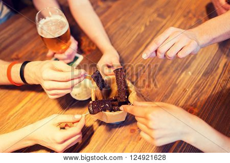 fast food, junk food, unhealthy eating and culinary concept - close up of people hands taking garlic bread snack with skewers at bar or restaurant