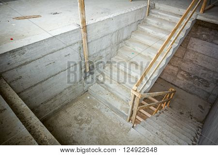 New concrete staircase with temporary wooden handrail under construction.
