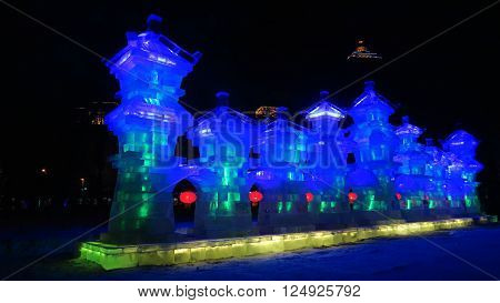 HARBIN CHINA - JANUARY 16 2016: colorful ice castle at night during the 32nd Harbin Ice Festival. The main attraction is the Harbin Ice and Snow World which covers more than 750000 square meters. Its structures required more than 330000 cubic meters of ic