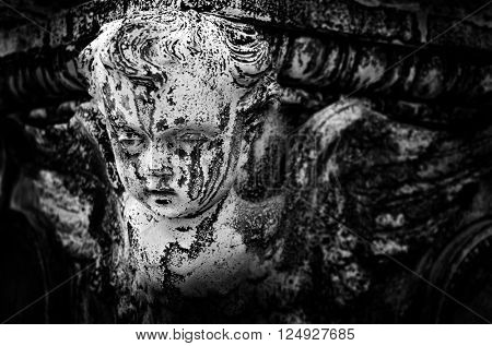 Antique marble statue of a Cherub angel with detail of the face