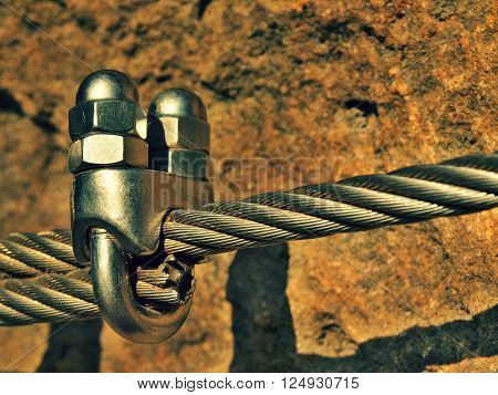 Steel bolt eye in the middle. Steel anchor bolt eye in sandstone rock. The fixed steel rope. Climbers path via ferrata. Iron twisted rope fixed in block.