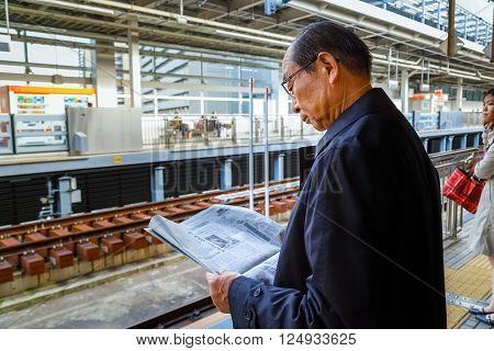 NAGOYA JAPAN - NOVEMBER 22 2015: Unidentified Japanese train commuter reads a newspaper while waits for a Shinkansen train on a platform at Nagoya station