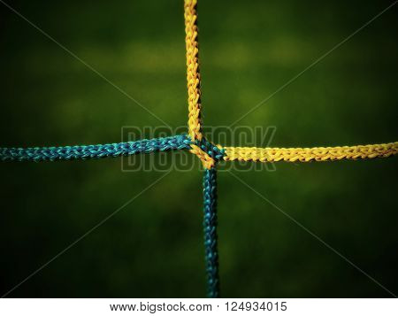 Detail Of Yellow Blue Crossed Soccer Nets, Soccer Football In Goal Net With Green Grass On Playgroun