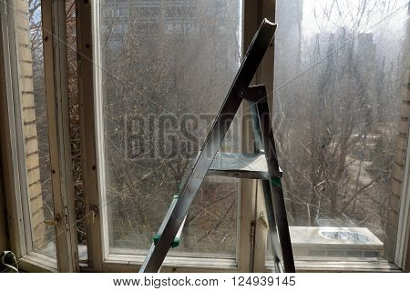 Ladder On A Background Of Old Windows