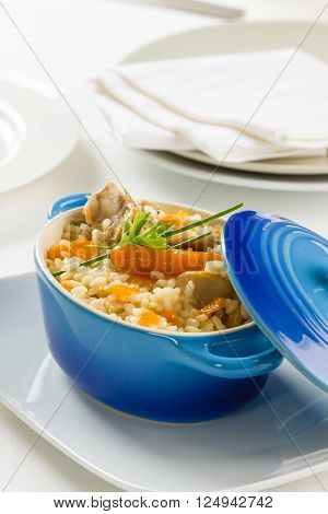 A small cooking pot with rice, vegetables and rabbit meat.