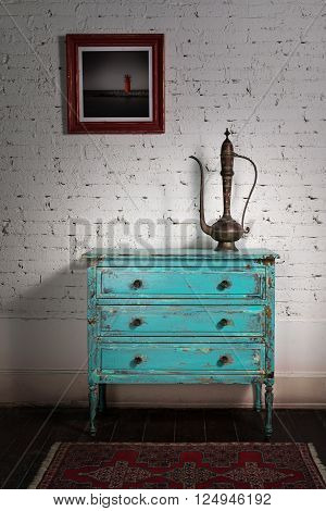 Retro composition of copper antique tea pot on green vintage cabinet with white bricks wall in studio