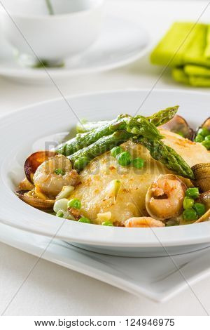 Hake with green asparagus, green peas, prawns and clams