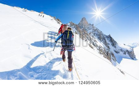 Mountaineers climb a snowy peak. In background the famous peak Dent du Geant in the Mont Blanc Massif, the highest european mountain. The Alps, Chamonix, France, Europe.