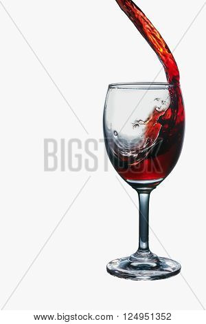 Red wine splash into glass isolated on white background.