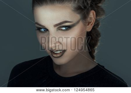 Gorgon medusa in dungeon. Young woman with creative fantasy hairstyle and make up for halloween
