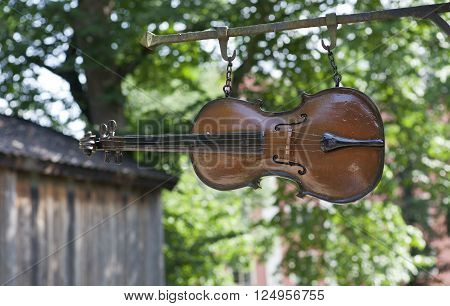 TURKU, ABO FINLAND ON JUNE 30. View of a wooden violin, fiddle in closeup hangs above a street on June 30, 2013 in Old Town, Turku, Abo Finland. Sign for a luthier.