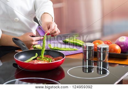 Closeup chef cutting green peppers on wooden surface with red skillet in front frying up vegetables.