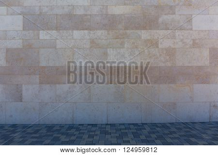 Stone wall brick wall with sidewalk in the shade with bright sunlight